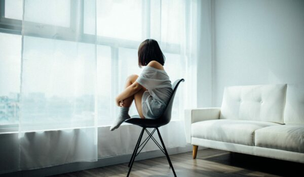 Woman sat on a chair, clutching her knees and staring our of a window feeling sad