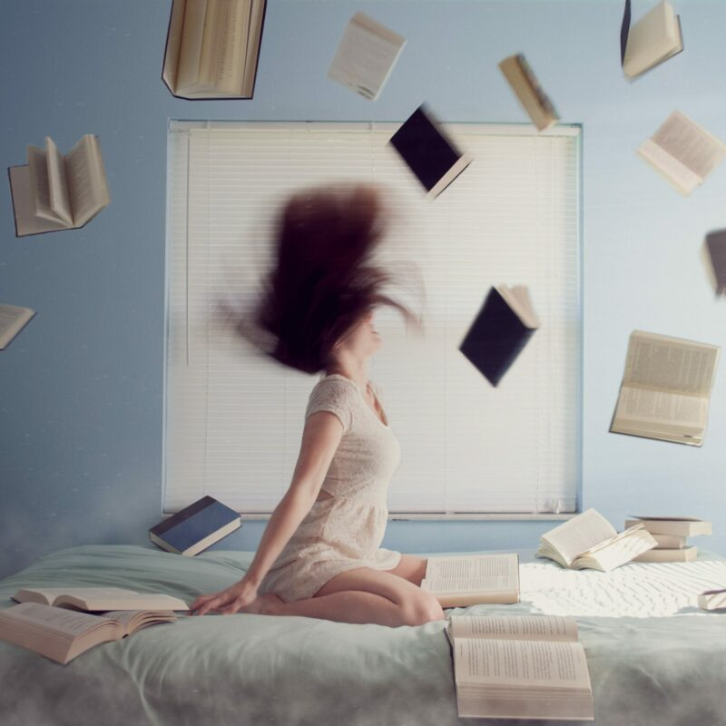 woman on her bed stressed out throwing books